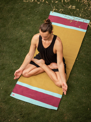 Yoga teacher sitting in padmasana on yellow herbal dyed yoga mat.Practice meditation under tree, wearing natural materials