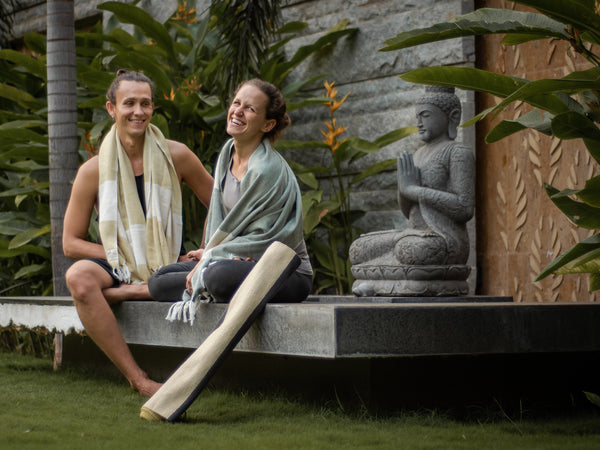 Smiling girl and boy are sitting in the garden close to the lake with Buddha statue. They are resting after yoga practice in the garden wrapped in handwoven herbal dyed towels. Cotton yoga mat is rolled on the side.