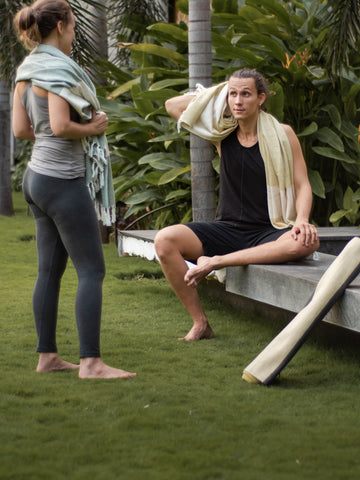yogis talking after practice in the garden using the meditation towels to cover themself and drying their yoga mats