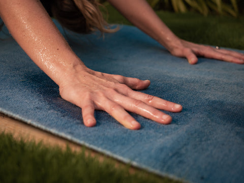 hands of girl practicing yoga hold perfect grip while sweating on yoga rug while staying in position downward facing dog