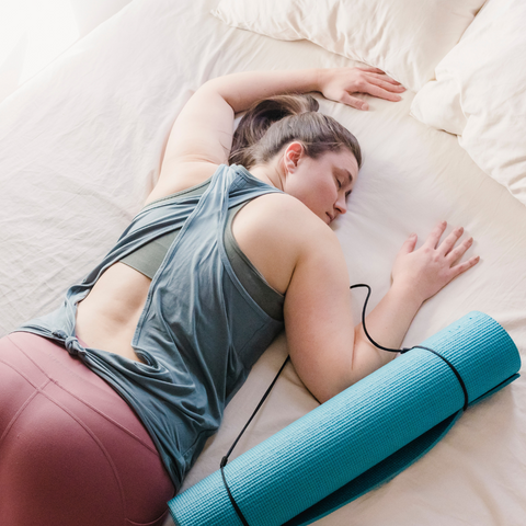 Woman sleeping on the bed with blue yoga mat next to her. Post yoga workout made her tired.