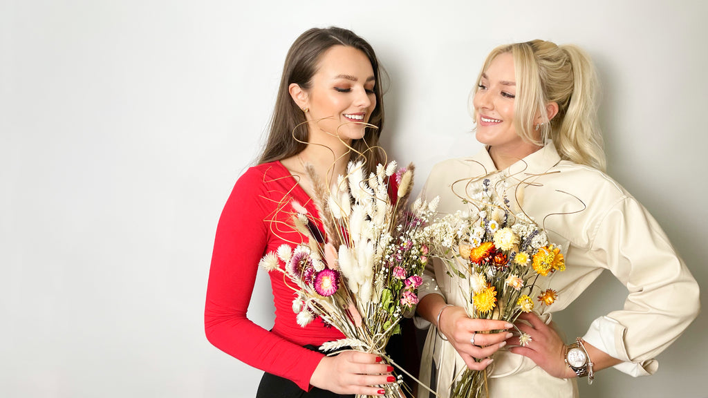 two girls holding dried flower bouquets