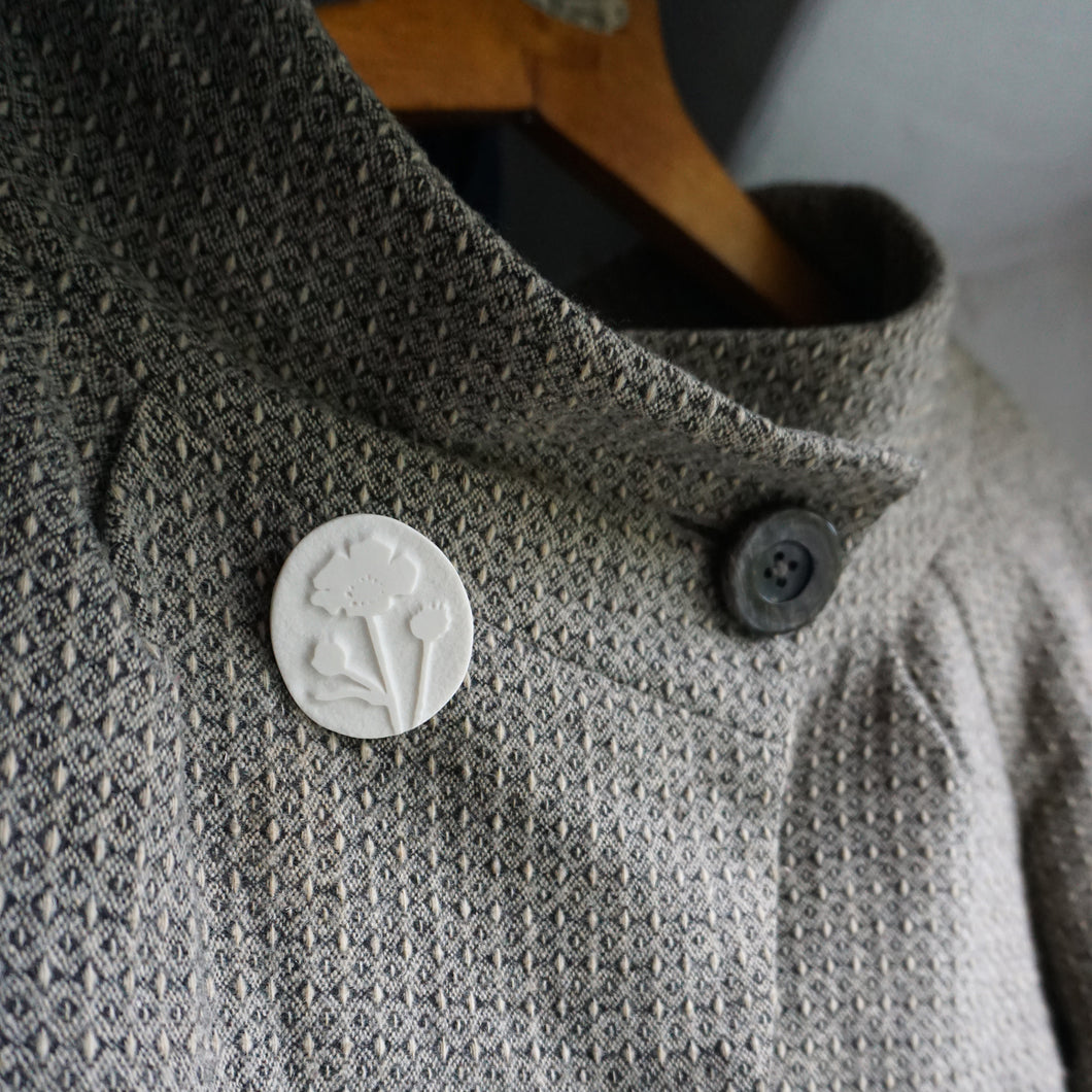 Dogtooth jacket with white porcelain brooch etched with buttercup design.