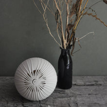 Load image into Gallery viewer, White spherical lamp, unlit with starburst fronds design, bottle with twigs on the right.