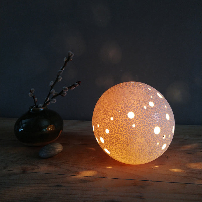 Spherical porcelain Lamp with holes and textured surface.