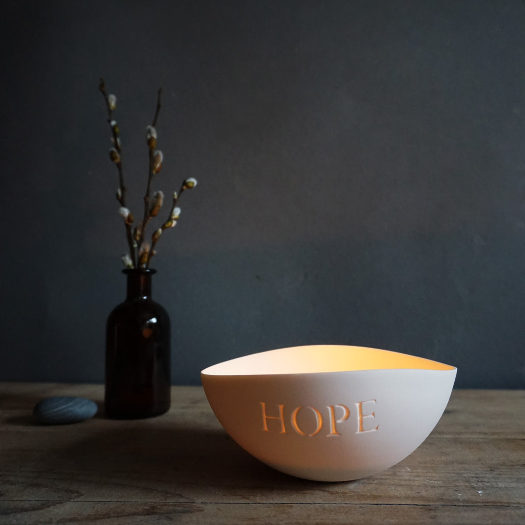 Porcelain bowl lit with a candle with HOPE etched into it, pebble and bottle with pussy willow on the left.