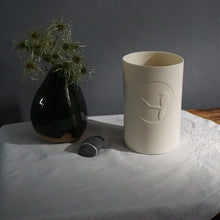 Load image into Gallery viewer, White beaker with magpie silhouetted in a bright circle. Vase and pebble on left.