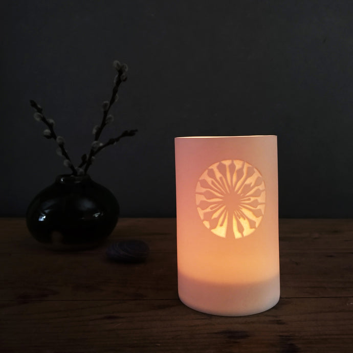 Ivy Flower glowing porcelain tealight beaker with vase in the background.