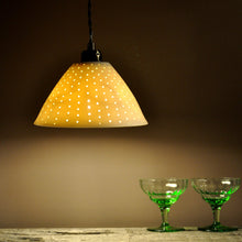 Load image into Gallery viewer, Orange sparkly bell shaped lampshade with small bright dots running from top to bottom. Two green glasses on the right.