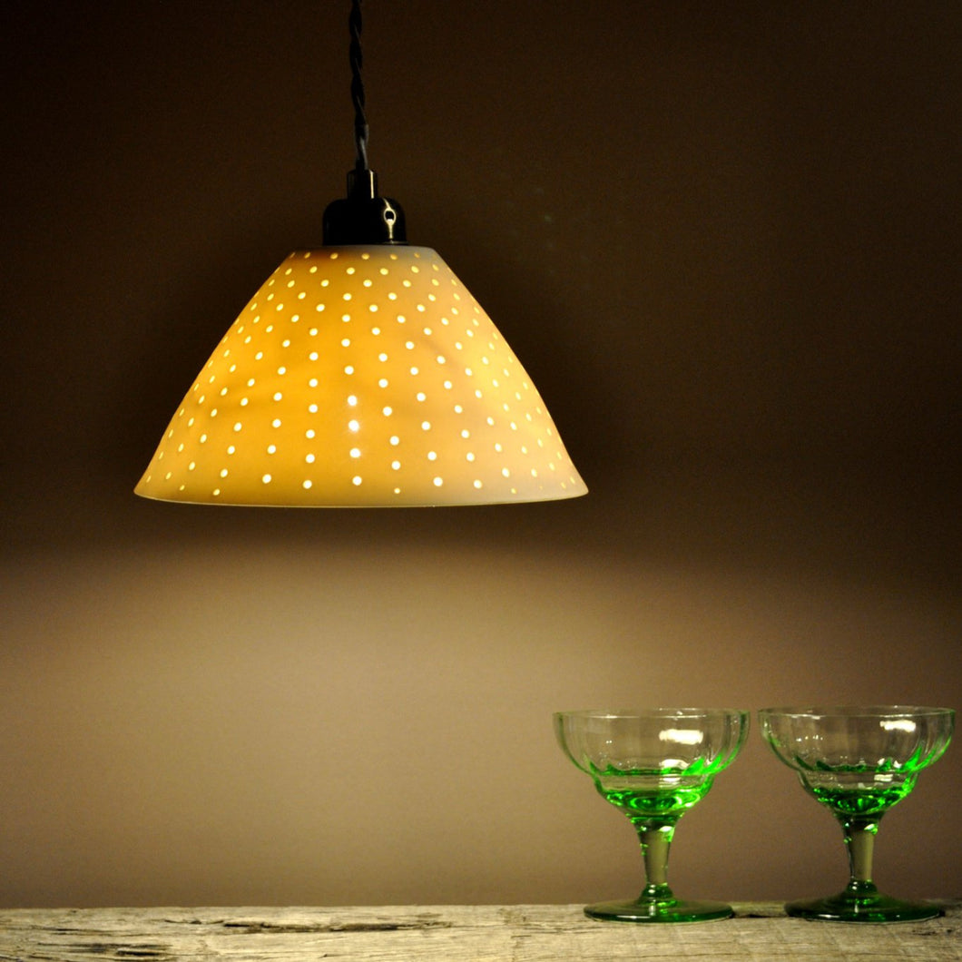 Orange sparkly bell shaped lampshade with small bright dots running from top to bottom. Two green glasses on the right.