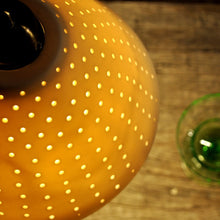 Load image into Gallery viewer, Orange sparkly bell shaped lampshade with small bright dots running from top to bottom seen from above. Two green glasses on the right.