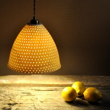 Load image into Gallery viewer, Orange sparkly bell shaped lampshade with small bright dots running from top to bottom. Three lemons on the table to the right.