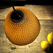 Load image into Gallery viewer, Orange sparkly bell shaped lampshade with small bright dots running from top to bottom seen from above. Three lemons on the right.