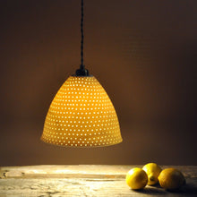 Load image into Gallery viewer, Orange sparkly bell shaped lampshade with small bright dots running from top to bottom. Three lemons on the right.