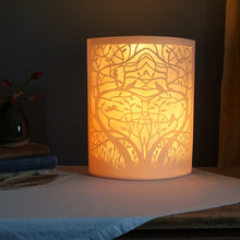 Load image into Gallery viewer, Porcelain lamp with symetrical entwined tree and birds in silhouette. Glowing warm orange.
