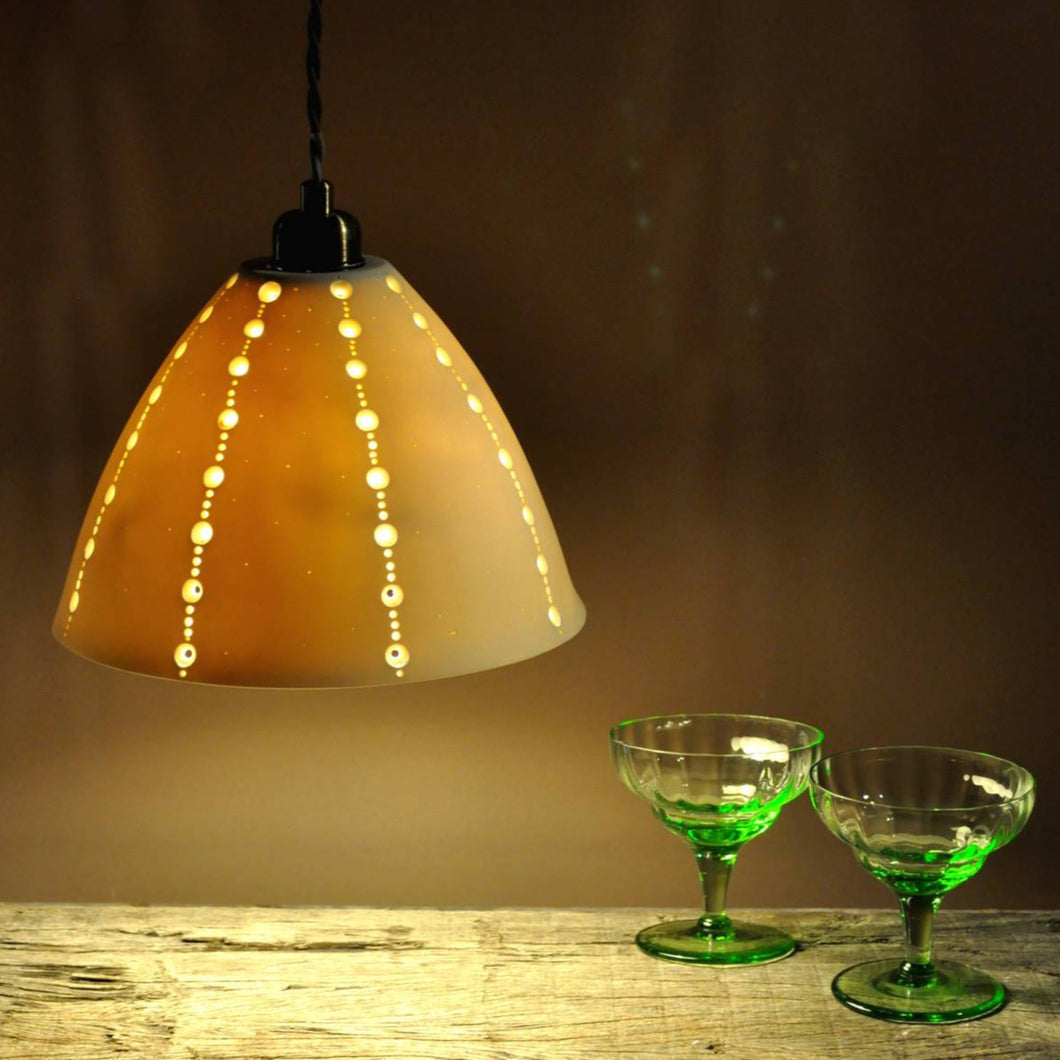 Orange glowing bell shaped lampshade with lines of brighter dots running top to bottom. two vintage green stem glasses on the right.