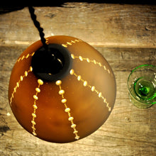 Load image into Gallery viewer, Overview of orange glowing bell shaped lampshade with lines of brighter dots running top to bottom. Vintage green stem glasses on the right.