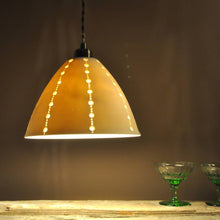 Load image into Gallery viewer, Orange glowing bell shaped lampshade with lines of brighter dots running top to bottom. Vintage green stem glasses on the right.