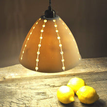 Load image into Gallery viewer, Orange glowing bell shaped lampshade with lines of brighter dots running top to bottom. Lemons on the right.