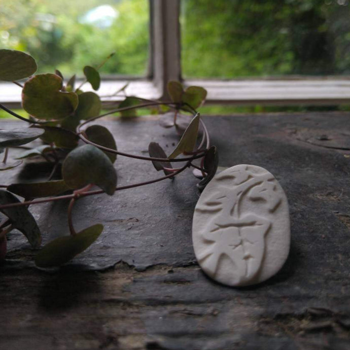 Oval white brooch with four Ivy leaves etched into it, displayed on a windowsill with a plant on the left.