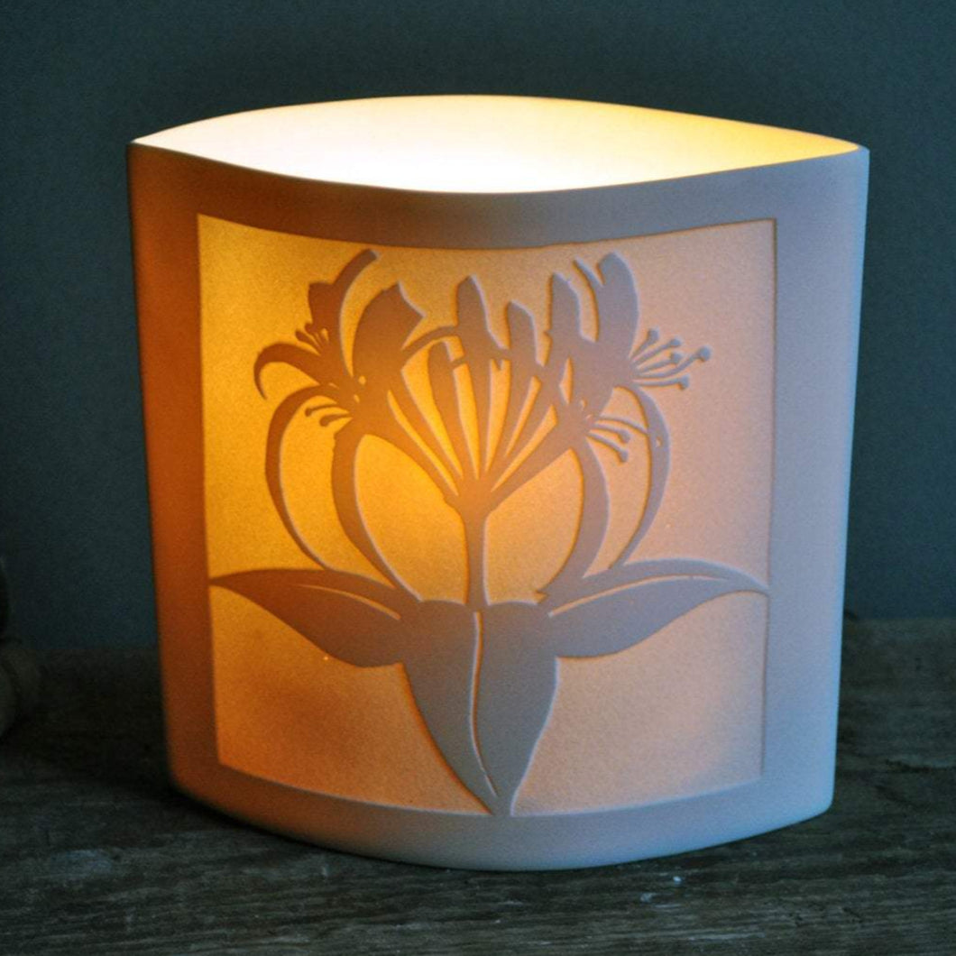 Square elliptical lamp depicting honeysuckle in silhouette, dark green background.