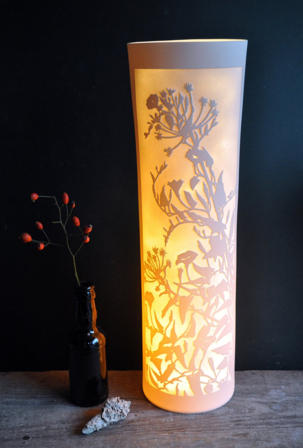 Cylinder Lamp, glowing orange depicting tangled bindweed hedgerow in silhouette. Bottle with rosehips and shell on the left.
