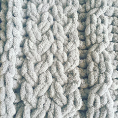 A close up of knitting detail showing grey chenille yarn in a braided pattern