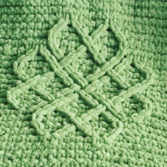 A close up of knitting detail showing green chenille yarn with a Celtic love knot design.