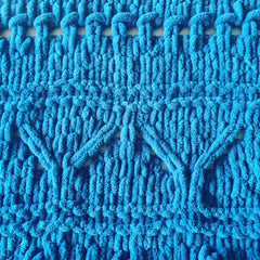 Close up of knitting detail showing blue chenille yarn in a southwest design.