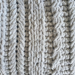A close up of knitting detail of grey chenille yarn in a mix of cable styles.