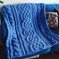 Blue chenille yarn Celtic cable blanket.