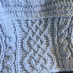 Close up of back panel of grey chenille Celtic cable shawl.