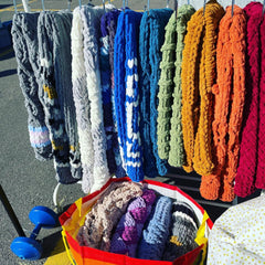 A rack of different colours of knitted chenille blankets, arranged in a rainbow