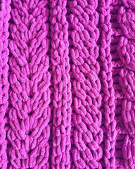 A close up of knitting detail showing berry pink chenille yarn with staghorn cables.
