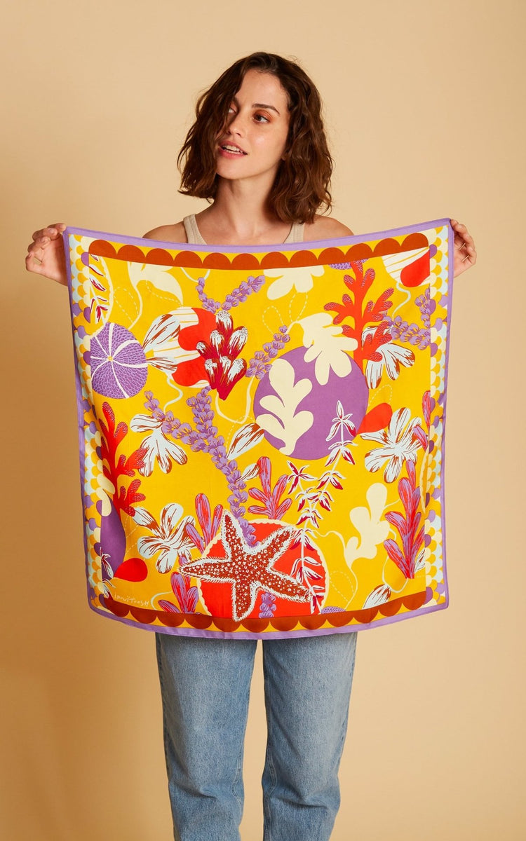 woman holding colorful silk scarf. orange, red, purple, and yellow flowers and sea scene. square silk scarf for neck or hair.