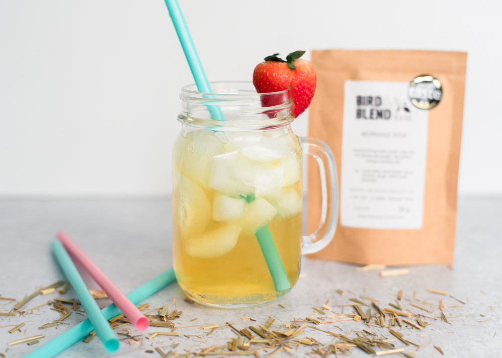 A glass of Morning Kick iced tea garnished with a strawberry