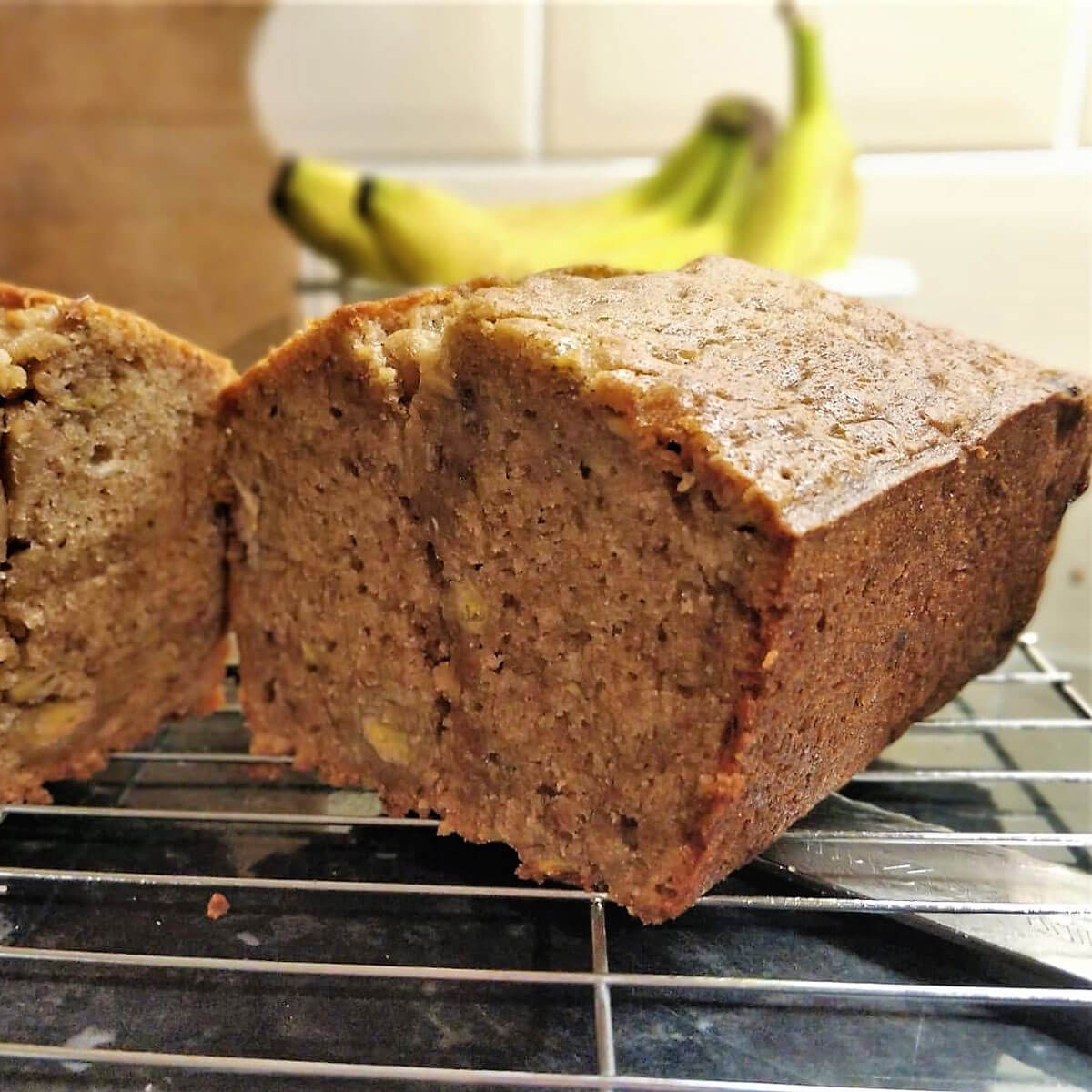 Final result of banana bread, sliced open with bananas in the background