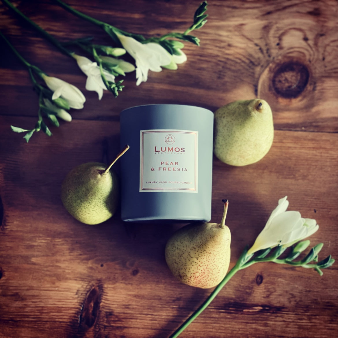 Pear & Freesia scented soy wax candle in a grey jar surrounded by fresh pears and freesia on a wooden table
