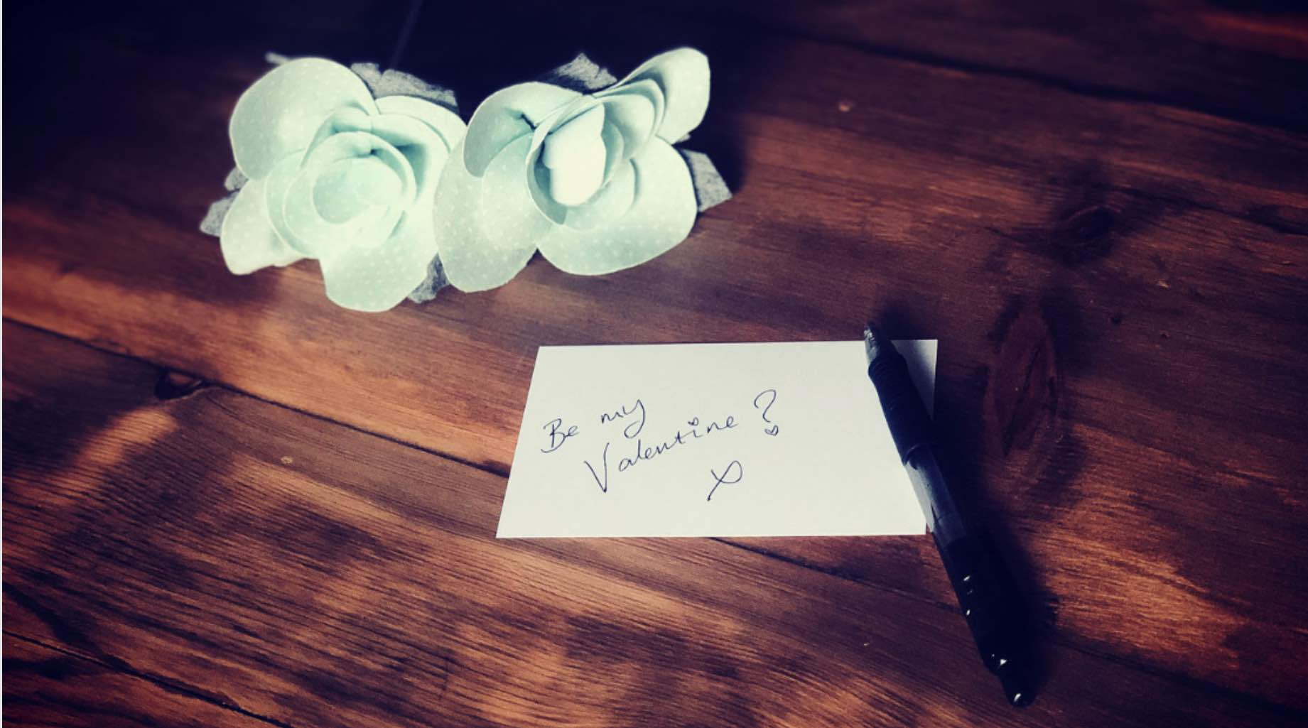 Be My Valentine. Blue Roses next to a gift card and pen with the words Be My Valentine written on