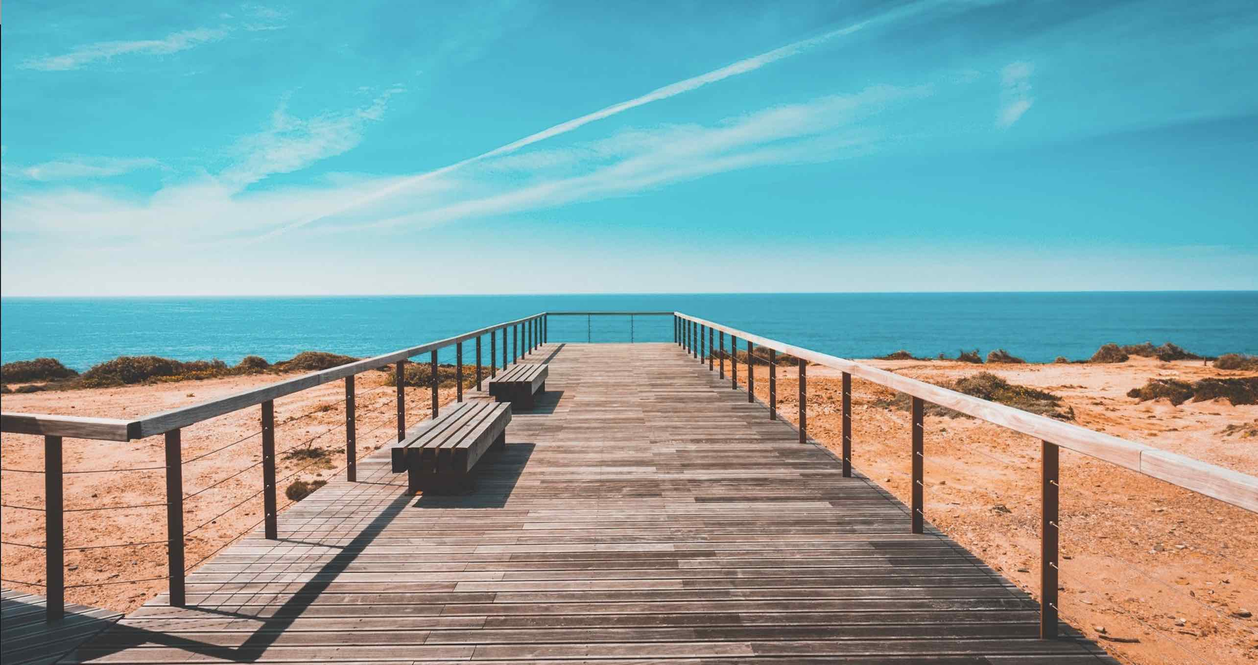 Panoramic beach view with a wooden path leading to golden sand and blue waters and sky