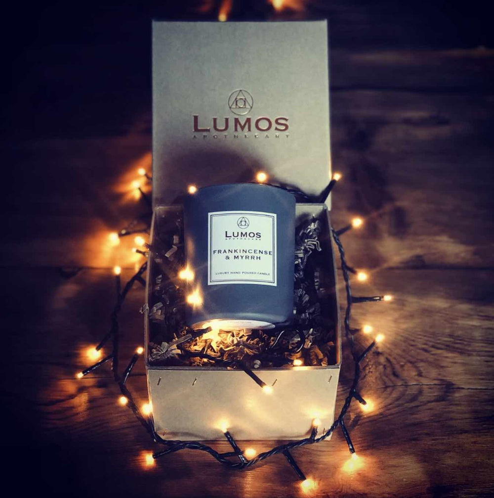 Monthly Candle Subscription Box UK, Grey Soy Wax Candle Jar in Hand Stitched Brown Box illuminated with fairy lights on wooden background.