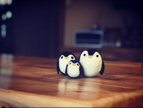Needle Felted Penguins on a wooden table