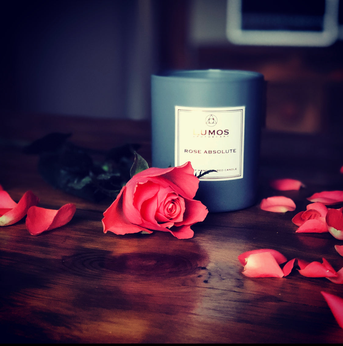 Rose Absolute Scented Natural Soy Wax Candle In Grey Jar Surrounded by red rose petals on a wooden table