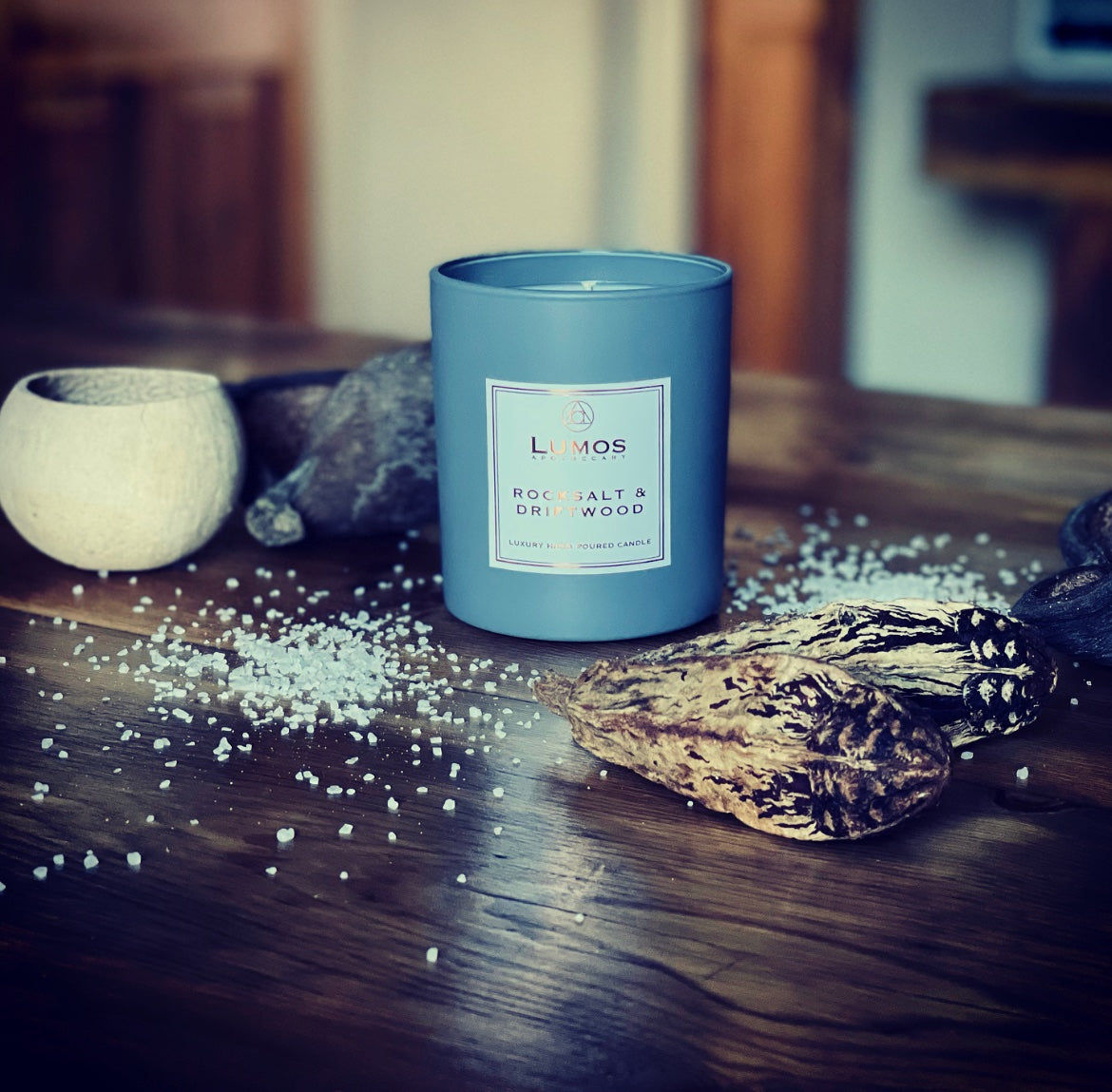 Rock Salt And Driftwood soy wax candle in grey jar on a wooden surface surrounded by salt and sea shells