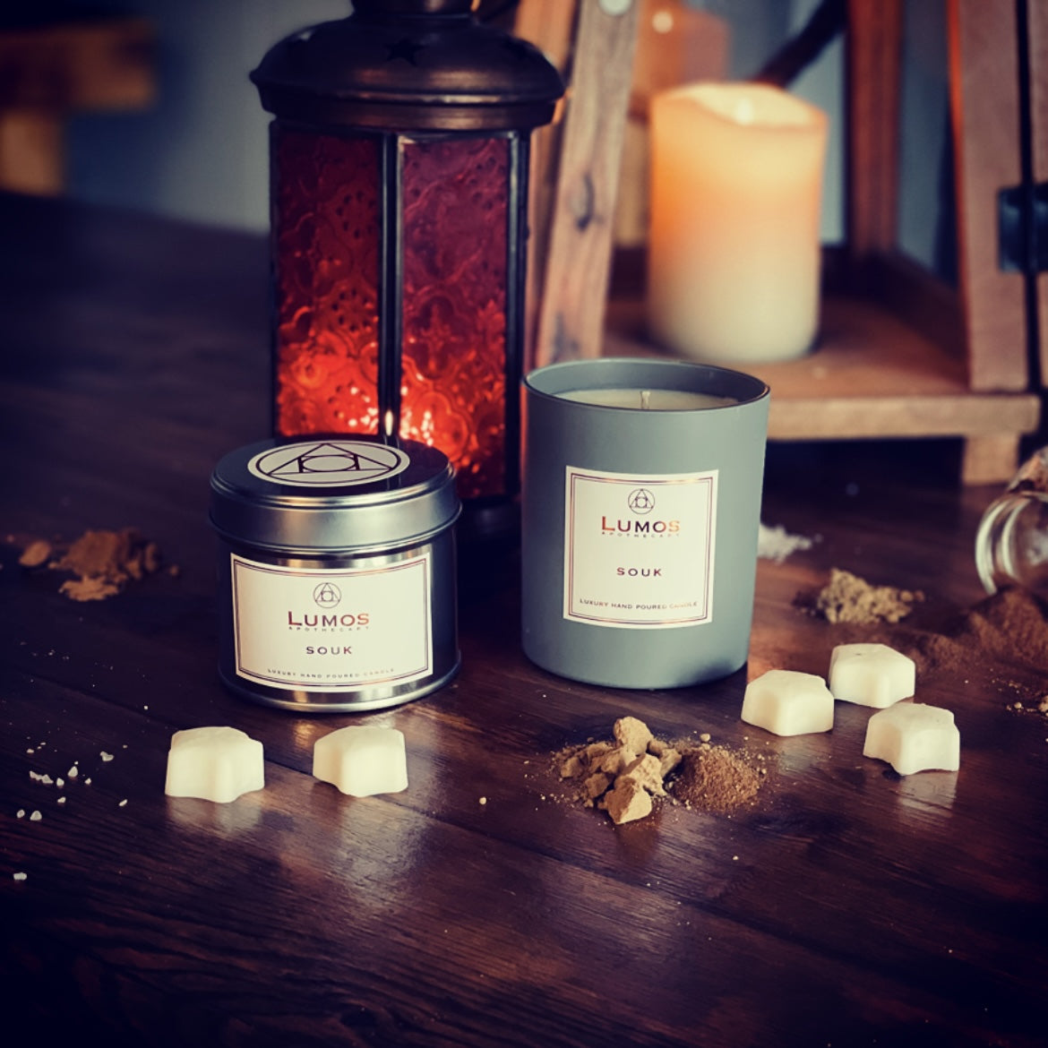 Persian Bazaar scented soy wax candle in a grey jar and silver tin surrounded by white wax melts on a wooden surface. A red lantern and pillar candle in the background.