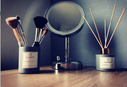 #CandleForLife A soy wax candle jar in grey repurposed as a macup brisk holder. With a mirror and grey reed diffuser bottle on a wooden surface