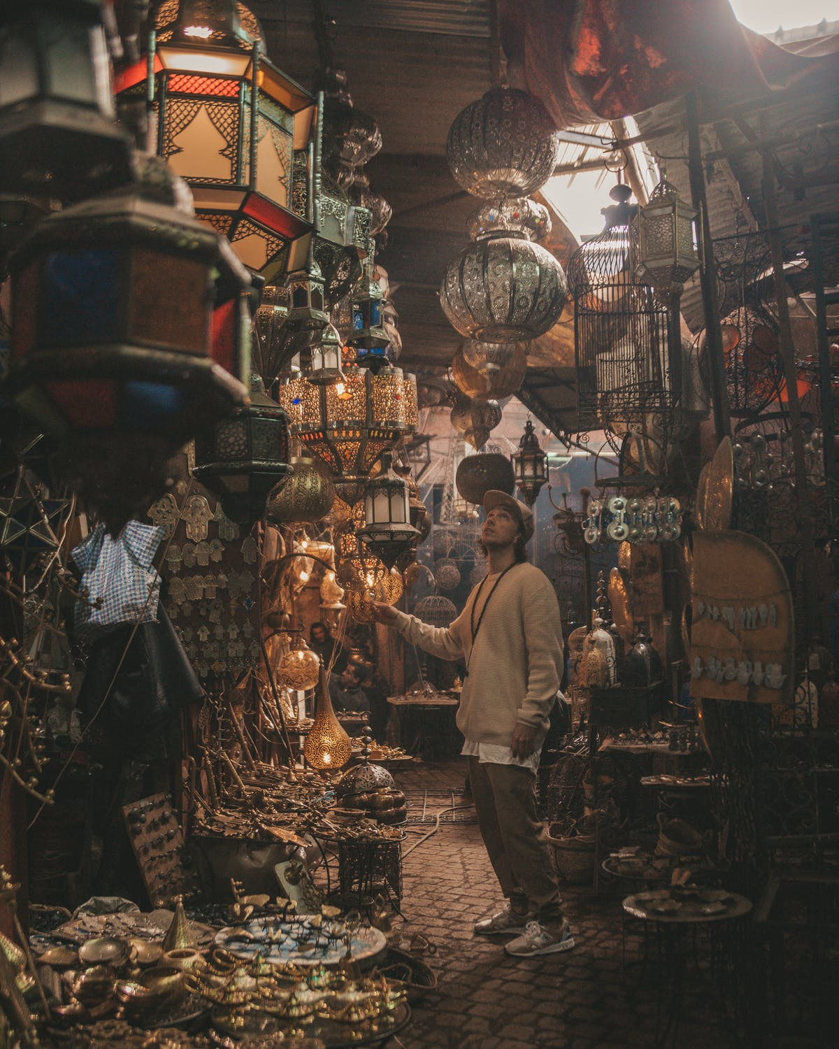 A man looks in wonder in a Persian bazaar upon old lanterns, rugs and spices