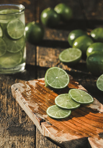 Sliced limes on wooden board with limes in water in a glass jar in the background