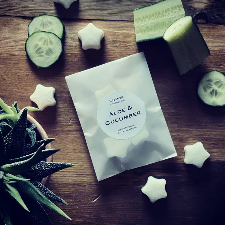 Aloe & Cucumber Scented Soy Wax Melts in a waxed bag on wooden table with Aloe Vera and chopped cucumber in the background