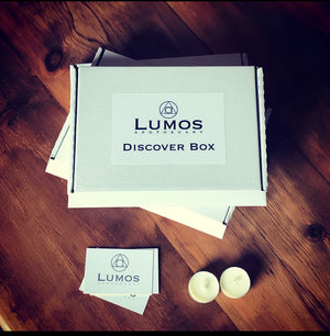 Monthly subscription box. A white cardboard box. Two tea lights on a wooden table with 3 lumos apothecary cards scattered around it
